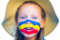 Laughing little girl in straw hat with painted face having fun