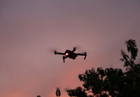 Flying drone against beautiful sunset sky