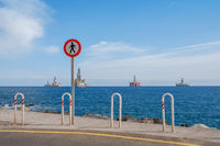 no trespass sign at end of road with ocean background,