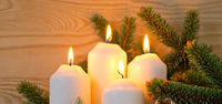 Christmas decoration and four burning Advent candles.