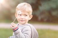 infant boy playing with dandelion