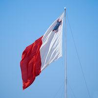 The flag of Malta fluttering over the Post of Castile in Birgu.