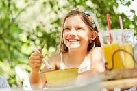 Lächelndes Mädchen isst Müsli zum Frühstück