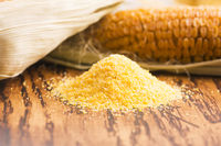 Corn groats and seeds, corncobs on wooden rustic table