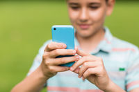 boy with smartphone outdoors at summer