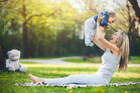 Delighted mother with her one year old son outdoors in a park