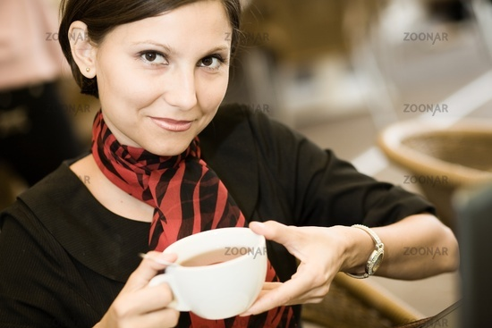 An image of a young woman with a big cup of tea