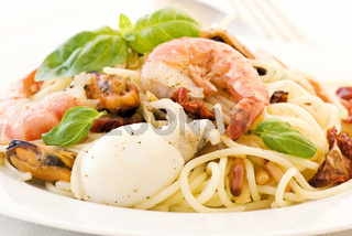 Spaghetti with shrimp, mussels and sepia as closeup on a white plate