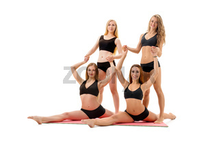 Slim sportswomen in tops and pants pose in studio
