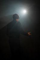 Man singing on dark smoky stage shot from back