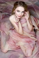 Naked beautiful woman draped in transparent dress.