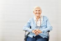 Lächelnde alte Seniorin sitzt im Rollstuhl