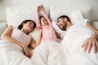 happy family waking up in bed at home