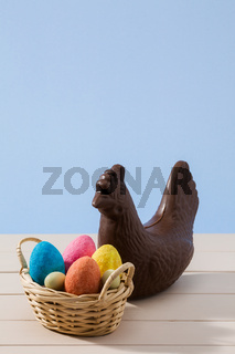 Easter chocolate chicken and colored eggs over a white table