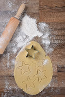 Top view of raw cookie dough with star shapes and cookie cutter on wood table with a rolling pin and