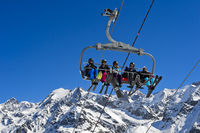 Skiers on a chair lift in the skiing area Les Contamines, Mont Blanc area, Haute-Savoie, Fr