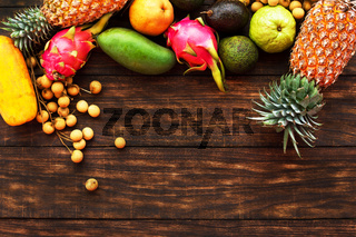 Tropical fruit on dark wooden background, top view