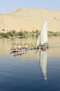 Egypt Aswan Boats Sailing Past Desert Landscape