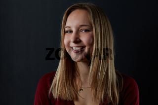 Lächelnde junge Frau vor dunklem Hintergrund