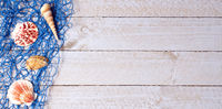 Shells with blue fishing net on wooden background