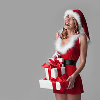Santa girl with stack of gifts