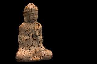 Vintage figure in meditation pose on black background