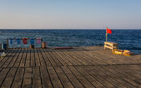 Red flag on wooden pier