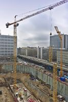 Construction site with excavation, machinery, cranes, road and high-rises in the backgrounf
