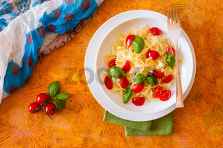Farfalle pasta with cherry tomatoes and basil seen from above