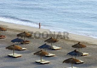 Einsamer Strandwanderer am Meeresufer vor strohgedeckten Sonnenschirmen und leeren Sonnenstühlen