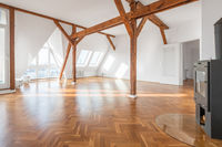 penthouse apartment interior ,  loft room with stove, parquet floor and roof beams