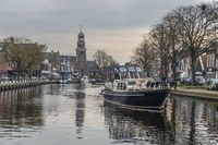 A motoryacht on the canal in the former fishing village Lemmer on the ice sea (IJsselmeer).