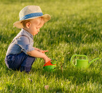 Toddler child outdoors. One year old baby boy wearing straw hat using watering can