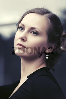 Beautiful fashion woman in black dress on city street