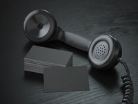 Mockup of black blank business cards and  black retro phone receiver  on  the black wooden desk background.