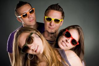 vier leute mit bunten brillen