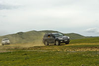 Two four-wheel-drive vehicles with tourists on a dusty dirt road, Mongolia