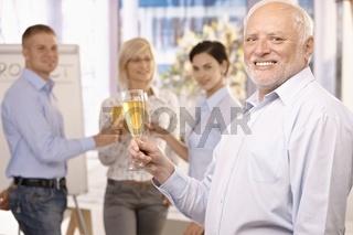 Senior businessman raising champagne glass