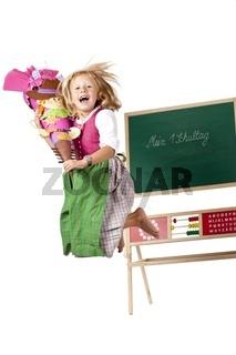 Mädchen mit Schultüte springt freudig am 1. Schultag in die Luft