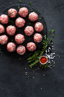 Raw meatballs on dark background, top view