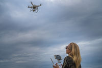 Happy woman taking photos with drone camera