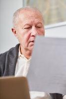 Senior liest aufmerksam ein Dokument