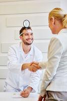 Patientin und Arzt geben sich die Hand
