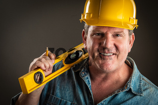 Smiling Contractor in Hard Hat Holding Level and Pencil With Dramatic Lighting.
