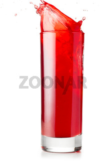 red liquid is spalsing in glass