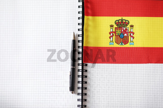 Learning foreign languages. Notepad for entries and a flag. Lang
