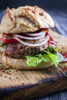 Barbecue Hamburger with Tomato and Salad Leaf on old Cutting Board
