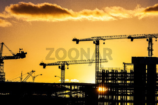 A beautiful view of cranes at counstruction site at sunset.