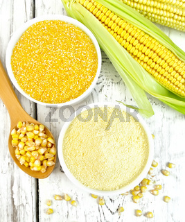 Flour and grits corn in bowls with grains on board top