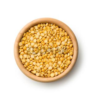 Yellow split peas in wooden bowl.